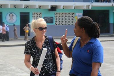 Kvinnlig volontär samtalar med personal vid besök vid skola på Jamaica där hon informerat om psykisk ohälsa.