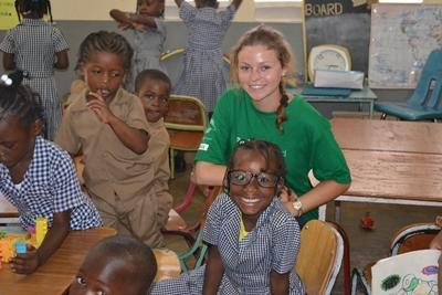 Volontär med barn utomlands flätar ung flickas hår, vid omsorgsprojekt.