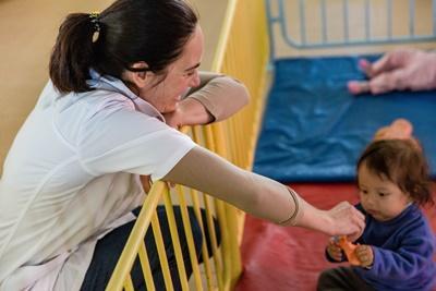 Kvinnlig socionompraktikant spenderar tid med barn vid barnhem i Cochabamba, Bolivia.