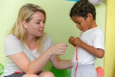Kvinnlig socionompraktikant spenderar tid med barn vid praktikplats i Ecuador.