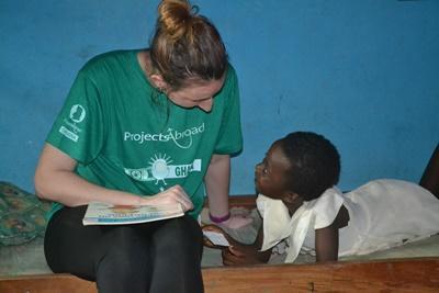 Kvinnlig socionompraktikant pratar med barn vid praktikplats i Ghana.