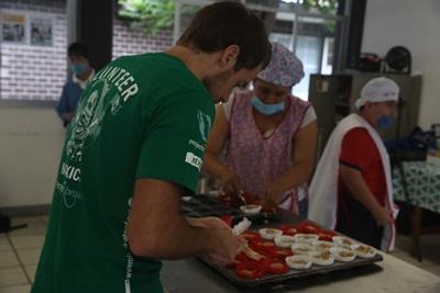Kvinnlig socionompraktikant äter frukost tillsammans med barn vid sin praktikplats i Mexiko.