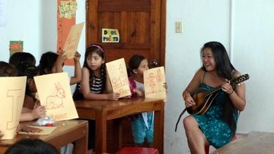 Volunteer on the performing arts project in Ecuador plays the guitar for school children