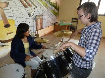 A local girl learns to play a musical instrument with the help of a volunteer in Bolivia.