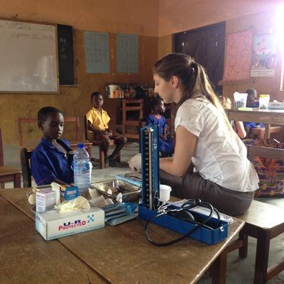 Volontär från Projects Abroad assisterar ung pojke vid medicinskt fältarbete i Ghana