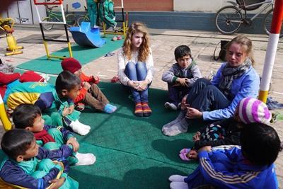 Kvinnlig volontär småpratar med barn under aktivitet i Nepal.