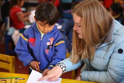 Volontär i Peru förklarar för ett barn hur man använder en sax.