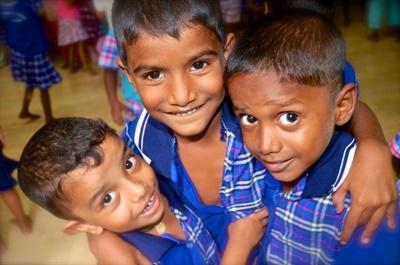 Tre barn poserar utanför sitt dagis på Sri Lanka