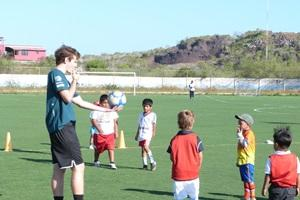 Volunteer leads a soccer practice as a sports coach in a school in Ecuador