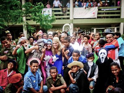 Gruppfoto med volontärer omringade av lokalbefolkning på Fiji