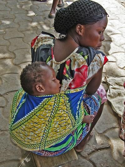 Woman with her child tied on to her back on the street in Togo