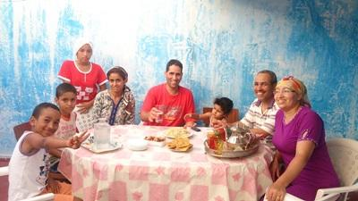 A Moroccan host family sit down to have a meal together
