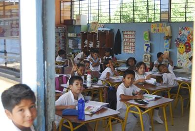 Students sit in a classroom where volunteer teachers work in Ecuador