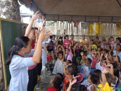 Volunteer teaches a song to a class of children at a school in the Philippines