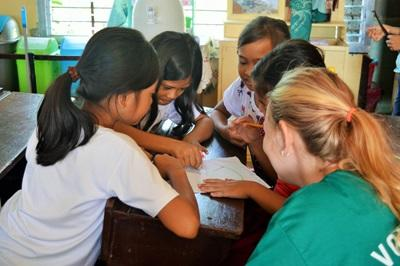 Volunteer working with children in a undervisning exercise in the Philippines