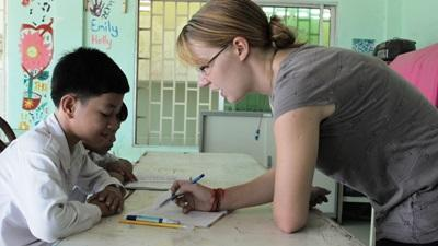A Cambodian child listens to a Teaching volunteer as she helps him with an activity