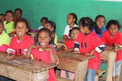 En grupp skolbarn sitter vid sina bänkar och inväntar dagens lektion vid en skola på Madagaskar