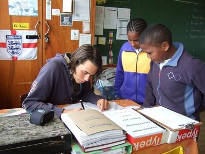 Volunteer on the Teaching project helps students with classwork in South Africa