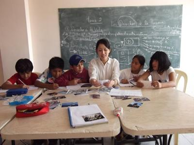 Teaching volunteer works on classwork with students in a school in Bolivia, South America