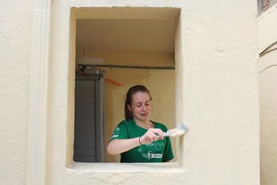 A teenage volunteer helps give a new house a coat of paint on the Building project in Mexico