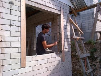 Ungdomsvolontär från projects Abroad arbetar med att sätta in fönsterkarm på ett hus vid byggprojektet på Filippinerna