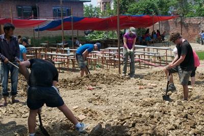 Grupp av ungdomsvolontärer gräver diken vid byggprojekt i Nepal.