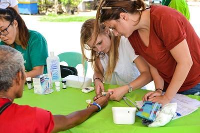 Ungdomsvolontär vid folkhälsoprojektet i Belzie tar blodvärden på patient vid fältarbete.