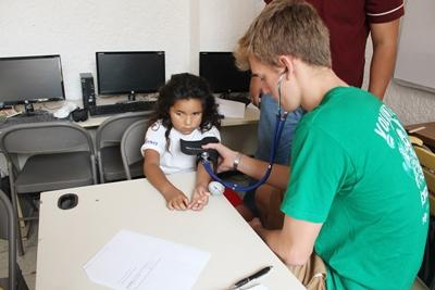 A Mexican child gets a health check conducted by a Projects Abroad volunteer.