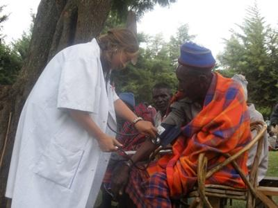 Teen volunteer works with disabled elderly woman on a Public Health project in Tanzania
