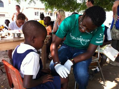 Teen volunteer treats child on a medical outreach program in a community in Ghana