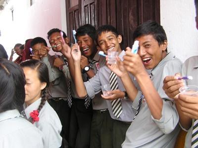 Elever vid skola poserar med tandborstar och tandkräm vd fältarbete på Sri Lanka med Projects Abroad.