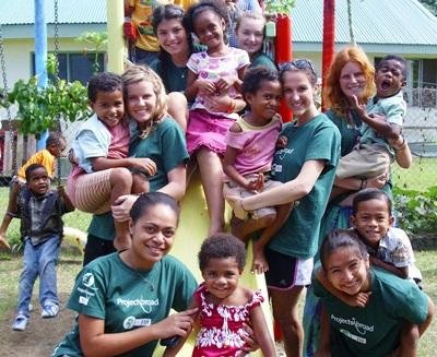 Volunteers and staff play on the playground with children on the Community Village project in Fiji