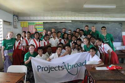 Gruppbild i klassrum med ungdomsvolontärer och elever på Samoa.