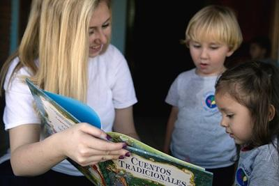 Care volunteer and the children of her care placement in Costa Rica enjoy story time together