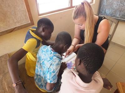 Volontär läser tillsammans med tre barn vid omsorgsprojekt i Togo.