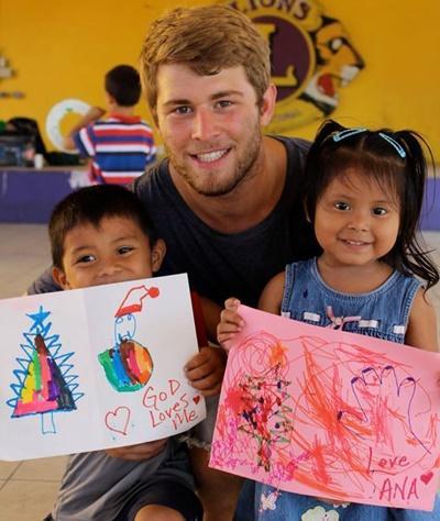 Ungdomsvolontär tillsammans med två barn som visar sina teckningar vid omsorgsprojekt i Belize.