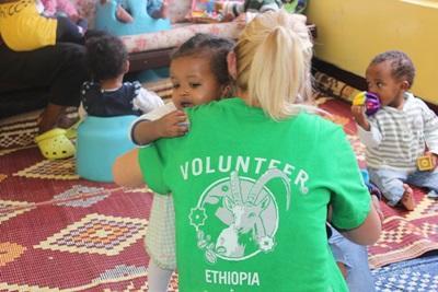 Kvinnlig volontär vid omsorgsprojekt i Etiopien kramar en liten flicka