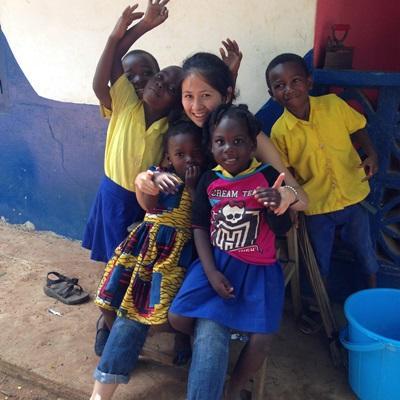 Kvinnlig volontär leker med barn vid omsorgsprojekt i Ghana