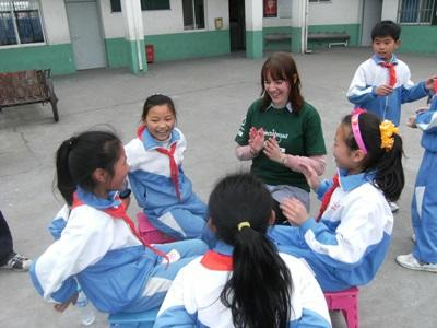 Teen volunteer plays patty cake with students during school break on a Care & Community project in China