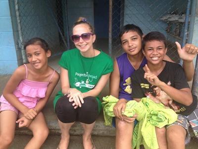 Ungdomsvolontär och tre samoanska barn poserar för bild vid projekt för omsorg och samhälle