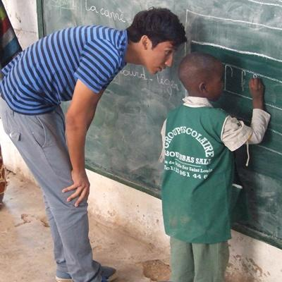 Teen volunteer helps young boy with classwork on the Care & Community project in Senegal