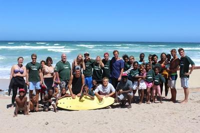 En grupp volontärer och barn på stranden i Kapstaden