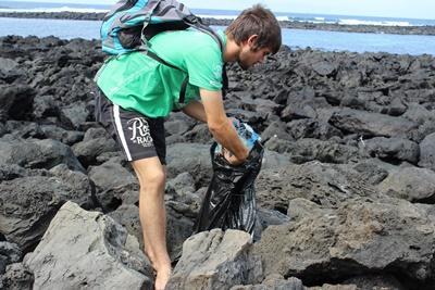 A male volunteer picks up litter on an Ecuadorian beach