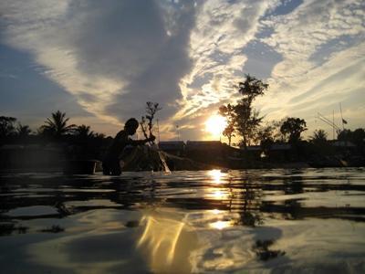 Fiskare i Kambodja försöker fånga sig något att äta i solnedgången.